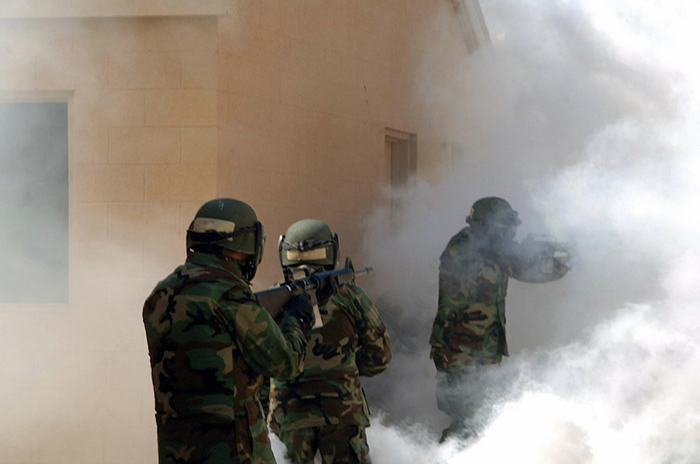 070530-M-6662M-090 CAMP LEJEUNE, N.C. (May 30, 2007) - U.S. Navy midshipmen walk through smoke during an assault against the urban terrain during career orientation training for midshipmen (CORTRAMID) at the military operations in urban terrain facility. CORTRAMID is designed to familiarize midshipmen with the missions, tasks, and equipment of the various warfare areas pertaining to surface, submarine, aviation, and Marine Corps. U.S. Marine Corps photo by Cpl. James McLaughlin (RELEASED)